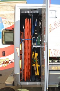 The rear compartment on the passenger side contains long board for spinal immobilization, a scoop stretcher, a Reeves stretcher, a stair chair, Hare traction devices, and a KED. Boards should always be secured using the blue strap. The tool compartment visible in the right of the photo holds two spare portable oxygen cylinders, the Big and Easy kit to gain entry into locked vehicles, and tools such as an ax and shovel.