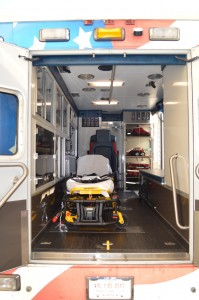 279's stretcher features an electronic lift component, making one person operation easier than the standard stretcher. The primary care provider sits on the bench in the right of the photo, and any additional support sits in the chair behind the head of the stretcher. The cabinet shown in the back right houses the portable oxygen bag, trauma bag, portable suction device, LUCAS Chest Compression System (not shown), pediatric attachment for the stretcher, AED, and mass casualty incident tags.